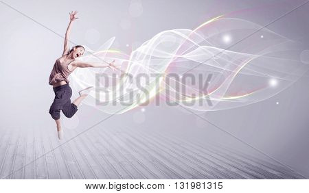 A beautiful young hip hop dancer dancing contemporary urban street dance in front of grey wall background with smokey lines and glitter concept. poster