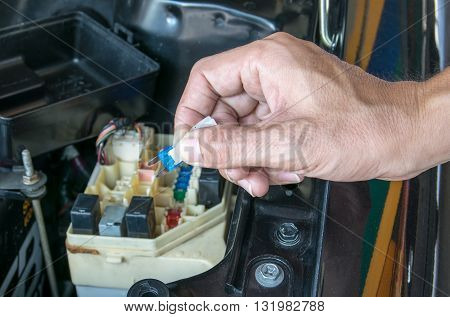 Auto mechanic checking a car fuse. car, fuse, automotive, electronics,