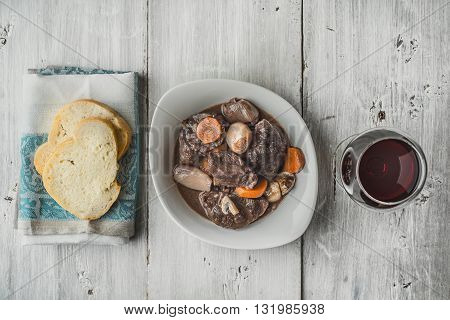 Beef bourguignon in a white ceramic dish with slices of baguette horizontal
