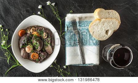 Beef bourguignon in a ceramic plate on a black stone and flower horizontal