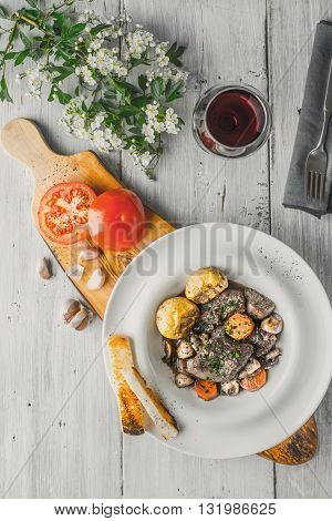 Beef bourguignon in a ceramic plate stand and white flowers vertical