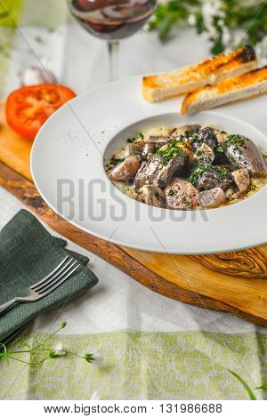 Beef bourguignon in a ceramic plate tablecloth tomato bread and grill vertical
