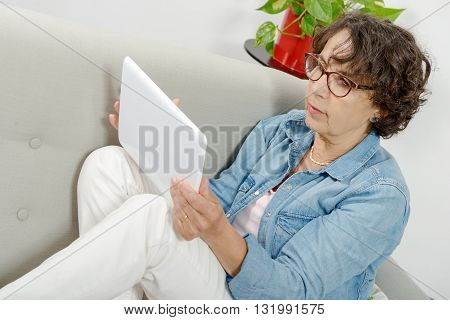 a beautiful mature woman with a tablet on the couch