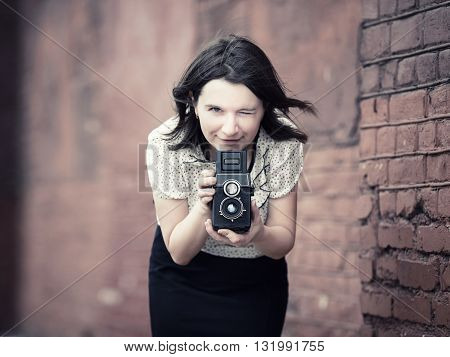 Woman with vintage camera in hands against blurred vintage brick wall background. Pretty young woman taking photo outdoors. Selective focus on the model's face and camera. Vintage style photo.