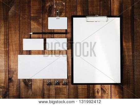 Blank stationery set on wooden table background. Letterhead business cards badge envelope and pencil. Top view.