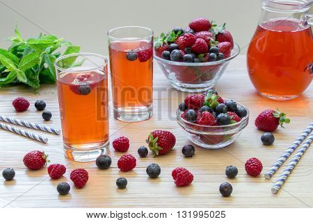 Two glasses of compote of raspberries strawberries blueberries near 2 bowls with berries mint leaves carafe compote on light wood background scattered berries. Fresh berries compote. Horizontal.