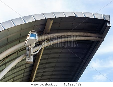 Old cctv camer under the metal roof of the train station.