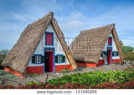 Old traditional Madeira explorer's houses at Santana - the symbol of Madeira island and touristic spot. Portugal.