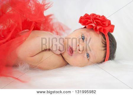 Surprised newborn baby girl dresses headband close-up