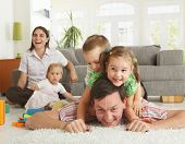 Happy family having fun on floor of in living room at home, laughing. poster