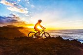 Mountain biking MTB cyclist woman cycling on bike trail on coast at sunset. Person on bike by sea in sportswear with bicycle enjoying healthy active lifestyle in beautiful nature. poster