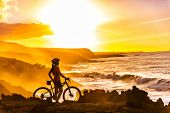 MTB cyclist mountain biking woman cycling looking at view on bike trail on coast at sunset. Person on bike by sea in sportswear with bicycle enjoying healthy active lifestyle in beautiful nature. poster