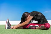Fitness woman stretching back and leg muscles with toe-touch stretches. Sporty young athlete doing a one leg seated forward bend yoga stretch on outdoor grass. Sitting head to knee fold over pose. poster