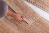 Installing laminate flooring. Carpenter lining parquet boards to each other fitting a plank poster