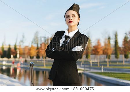 Beautiful Young Woman Stewardess In Uniform Looks Up To The Sky And Waits For Her Flight In The Park