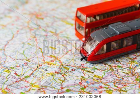 Travelling Abroad Background. Red Doubbledecker And Train On The Map. Tourism, Vacation And Business