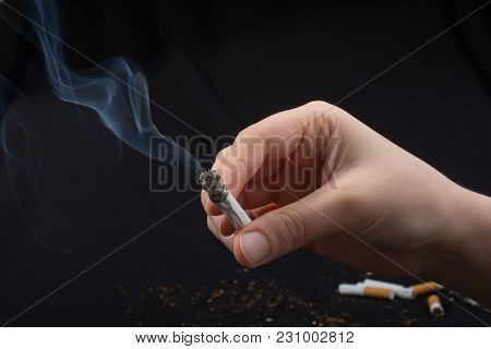 Hand Is Holding Smoking Cigarette With Smoke Around