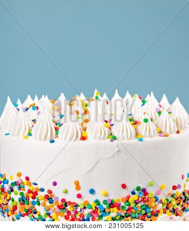 Side Of A Vanilla Buttercream  Birthday Cake With Colorful Sprinkles Over A Blue Background.
