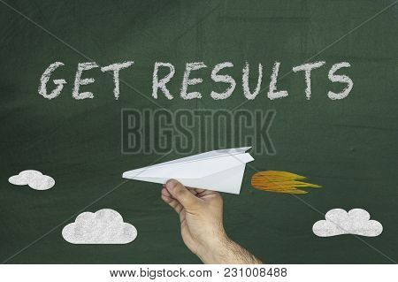 Hand Holding Flying Paper Airplane And Text Written On Blackboard: Get Results.