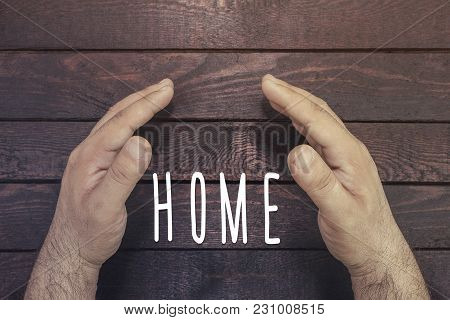 Person Holding Protective Hand On Home Text On Wood. High Angle View.