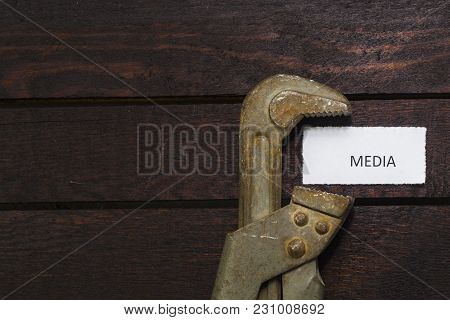Pipe Wrench Compresses A Piece Of Paper With An Inscription Media. Restricted Freedom Of Speech Symb