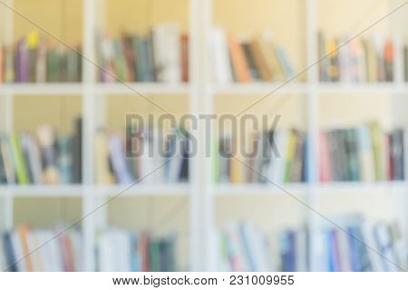 Abstract Blurred White Bookshelves With Books, Manuals And Textbooks On Bookshelves In Library Or In
