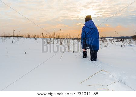 The Boy Is Walking On The Snow, Teenager In A Blue Winter Jacket And A Black Hat Goes Through The Bi