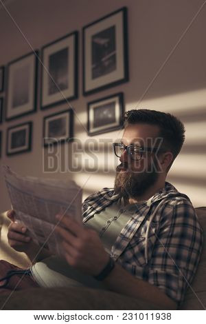 Handsome Young Man Sitting On A Living Room Sofa, Reading The Newspapers
