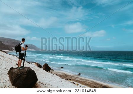 Photographer With Stative And Camera Staying On The Rock And Enjoying Coastal Landscape Of Sand Dune