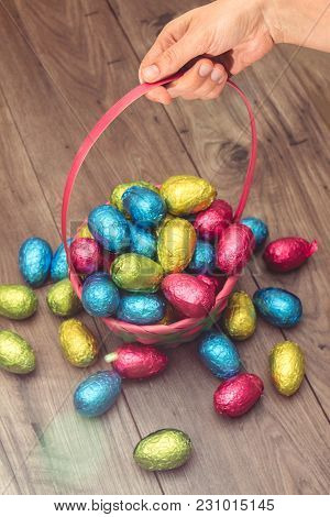 Hand Picking Up A Straw Basket Filled With Easter Chocolate Eggs Wrapped In Colorful Tinfoil On Top