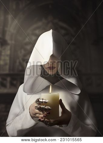 Sorceress in white hooded cloak holding a burning candle standing in the castle. poster