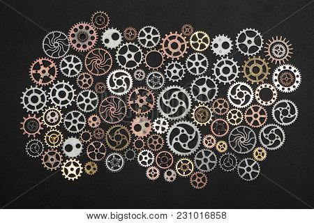 Bunch of cogwheels on a black background. Mechanism and industrial equipment. Spare parts.