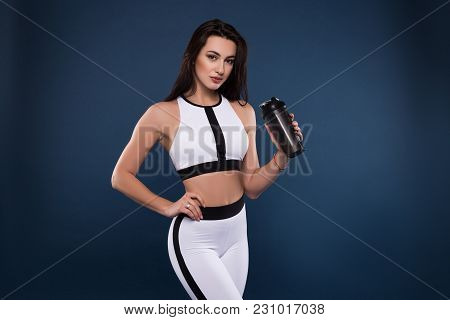 Stay Strong And Fit. Attractive Young Sporty Woman With Protein Shake Bottle On Dark Blue Background