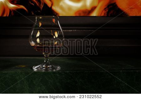 Glass Glass With Alcohol Reflects The Flame Standing On The Fireplace In The Evening Beautiful Inter