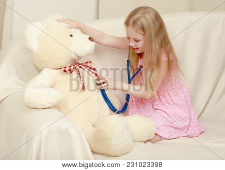 Beautiful Little Girl Is Playing Doctor. She Listens Through A Phonendoscope Of A Teddy Bear. The Co