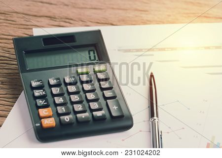 Pen And Calculator On Graph And Quarterly Chart Paper With Artificial Light, Kpi Or Financial Analys