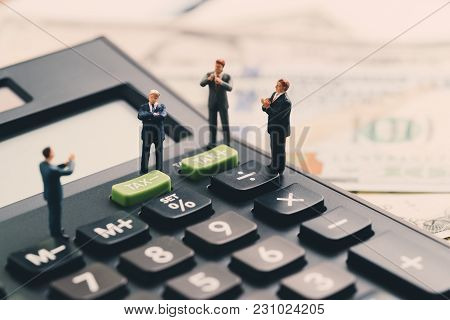 Miniature Figure, Leader Businessman Standing On Calculator With Others People Clapping On Business