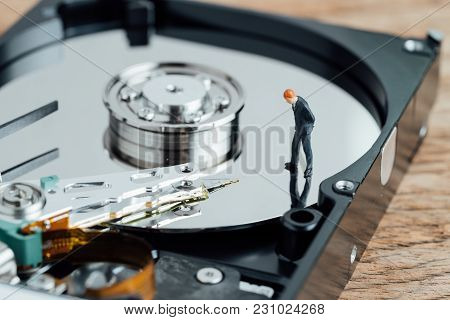 Data Analysis Concept, Miniature People Businessman Standing And Looking At Hard Disc Drive Platter,
