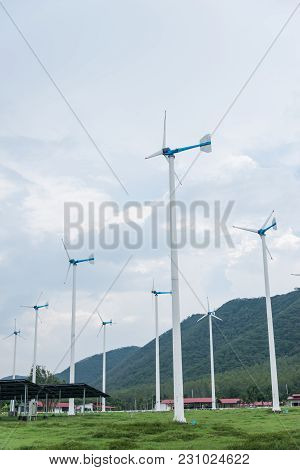 Wind Turbines Generating Electricity On Sky Background With Green Meadow Near Mountain