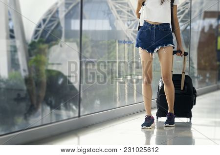 Young Woman In Airport Waiting For Air Travel Using Smart Phone. Travel Concept .