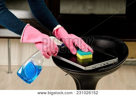 Wiping The Laptop Cover With A Sponge And Cleaning Liquid.hands In Pink Gloves Holding A Sponge And