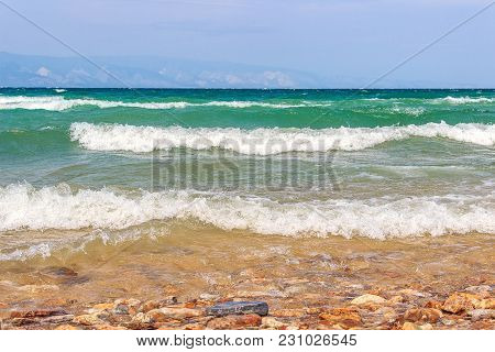 Landscape With The Image Of Clear, Windy Weather And Waves On Lake Baikal. Pebble Beach Of The Islan