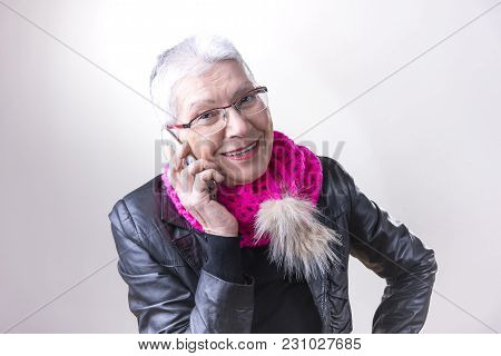 Fashionable Senior Elderly Woman Talking On Her Cell Phone, Feeling Happy And Cheerful, Studio Image