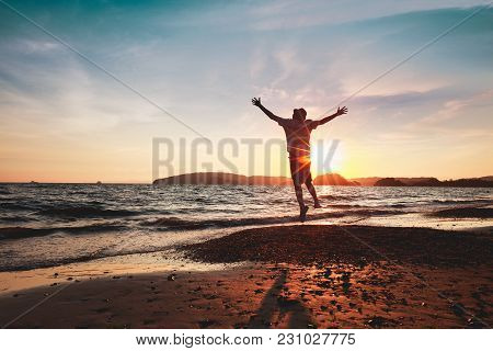 Male Tourist Running On Background Of Sunset Beach And Sea