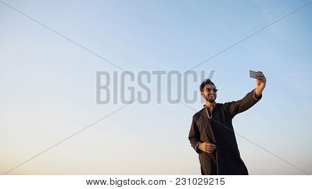Stately Muslim Tourist Guy Photographed On Front Camera Of Phone And Does Selfie, Smiling And Showin