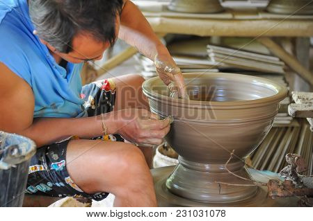 Sukhothai, Thailand - July 10, 2011: Senior Craftsman Making Ceramic Pottery From Clay By Using Elec