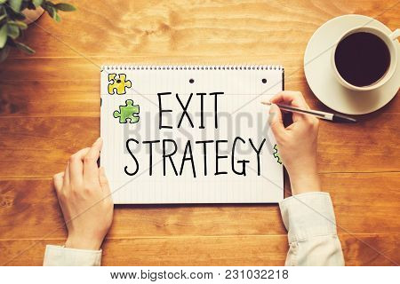 Exit Strategy Text With A Person Holding A Pen On A Wooden Desk