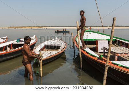VARANASI, INDIA - MAR 13, 2018: Boatmen on the banks of Ganga river. One of the oldest cities in the world, considered a Holy city for Buddhists and Jains, as the center of Earth in Hindu cosmology.