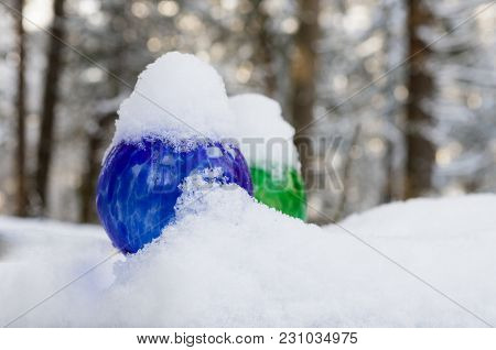 Colorful Watering Globes Covered In Fresh Snow On A Winter Day With Trees In The Background