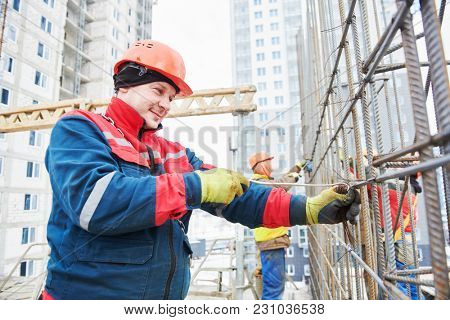 Concrete reinforcement. Builder knitting metal rods with wire
